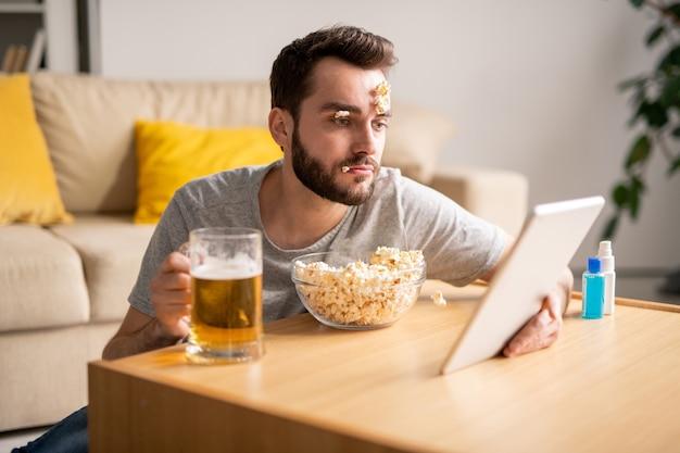 Jeune homme barbu endormi avec des pop-corn sur le visage, boire de la bière et regarder un film sur tablette, journée paresseuse en quarantaine