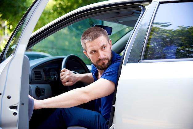 Un jeune homme barbu est assis dans une voiture avec une porte ouverte et regarde en arrière.