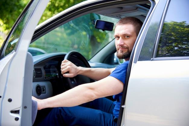 Un jeune homme barbu est assis dans une voiture avec une porte ouverte.