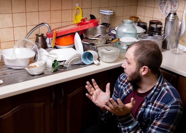 Un jeune homme barbu est assis sur le sol et est choqué par la quantité de vaisselle sale se trouvant dans l'évier de la cuisine à laver.