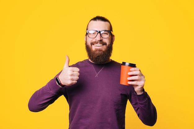 Jeune homme barbu est souriant et tenant une tasse de boisson chaude et montrant un tumb up