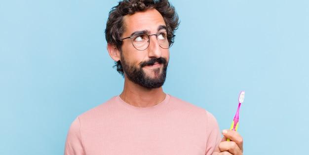 Jeune homme barbu avec une expression inquiète, confuse et désemparée, regardant pour copier l'espace, doutant