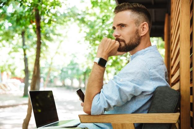Jeune homme barbu à l'extérieur à l'aide d'un ordinateur portable et d'un téléphone mobile