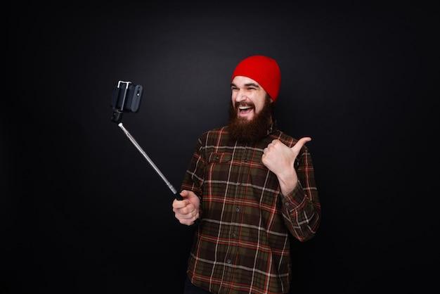 Jeune homme barbu faisant un selfie avec un bâton de selfie et montrant le pouce vers le haut.