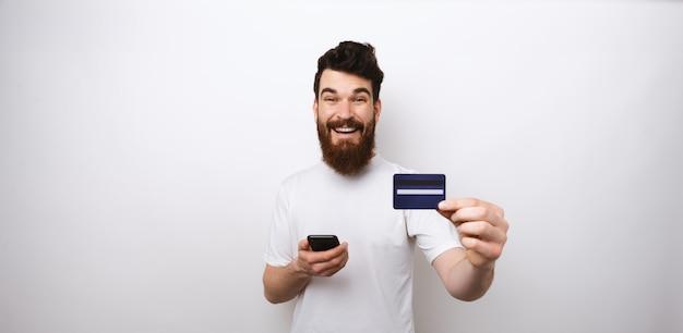 Jeune homme barbu fait ses achats en ligne ou utilise les services bancaires mobiles ou internet.