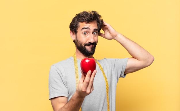 Jeune homme barbu fou au régime doutant ou expression incertaine et tenant une pomme