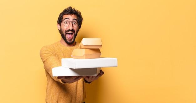 Jeune homme barbu fou ayant emporter la restauration rapide avec un espace de copie