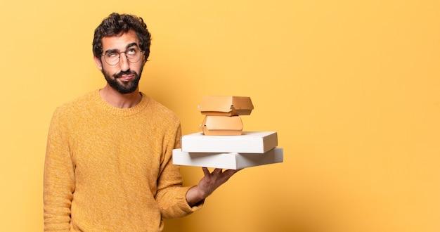 Jeune homme barbu fou ayant à emporter de la restauration rapide avec un espace de copie