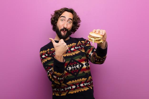 Jeune homme barbu fou ayant un hamburger