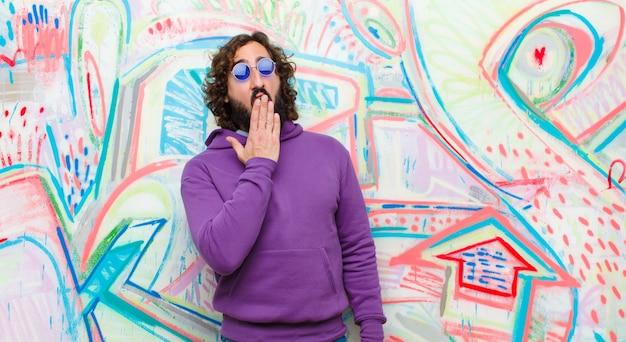 Jeune homme barbu fou bâillant paresseusement tôt le matin, se réveillant et ayant l'air endormi, fatigué et s'ennuyant contre le graffiti