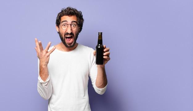 Jeune homme barbu fou avec une bière
