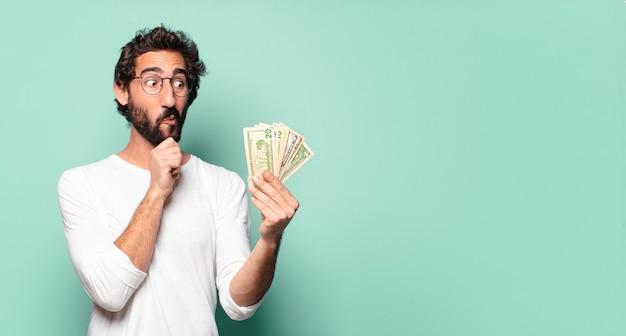 Jeune homme barbu fou avec des billets en dollars