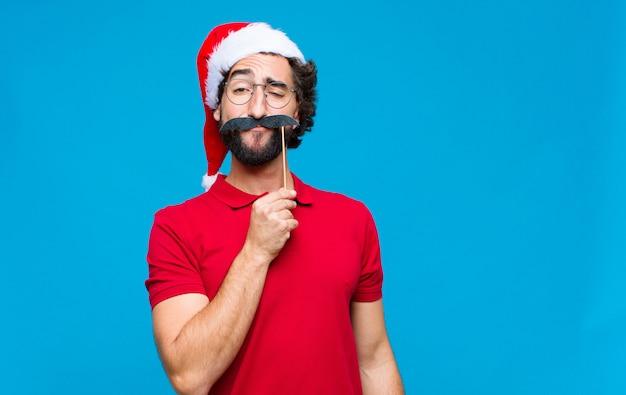 Jeune homme barbu fou avec bonnet de noel. concept de noel