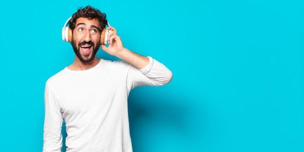 Jeune homme barbu fou avec un casque d'écoute de la musique