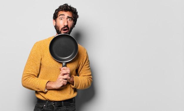 Jeune homme barbu fou avec une casserole. concept de cuisinier