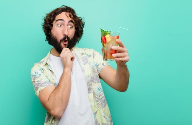 Jeune homme barbu fou avec un cocktail. concept touristique