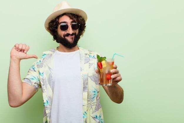 Jeune homme barbu fou avec un cocktail. touristique