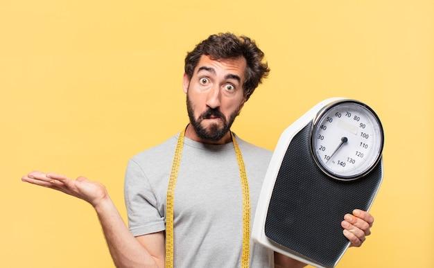 Jeune homme barbu fou doutant avec une expression incertaine et tenant une balance de poids