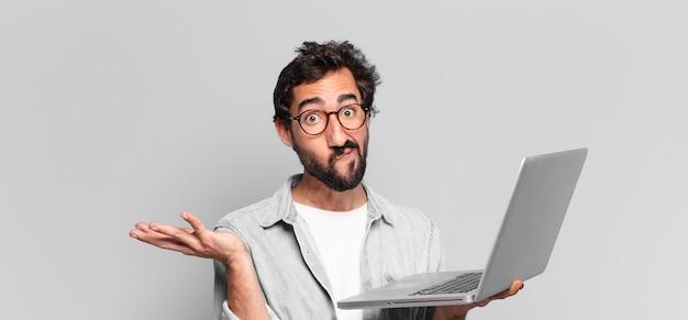 Jeune homme barbu fou expression effrayée ou confuse. concept d'ordinateur portable