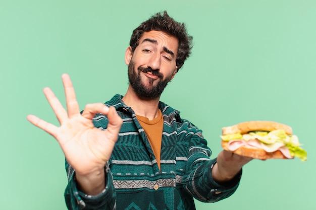 Jeune homme barbu fou avec une expression heureuse et tenant un sandwich