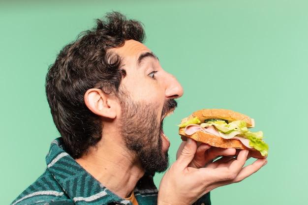 Jeune homme barbu fou expression heureuse et tenant un sandwich