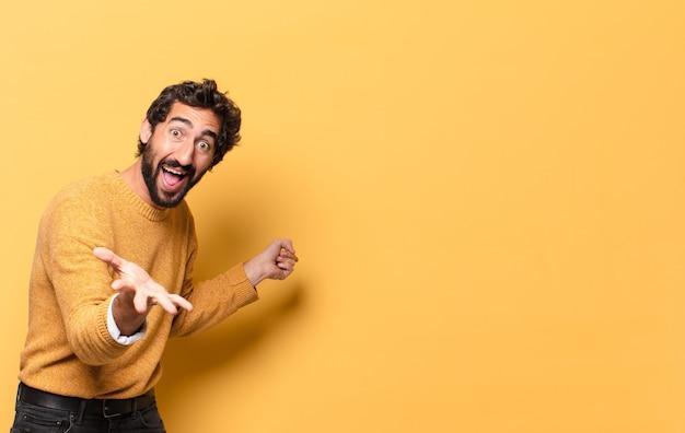 Jeune homme barbu fou exprimant avec un espace de copie