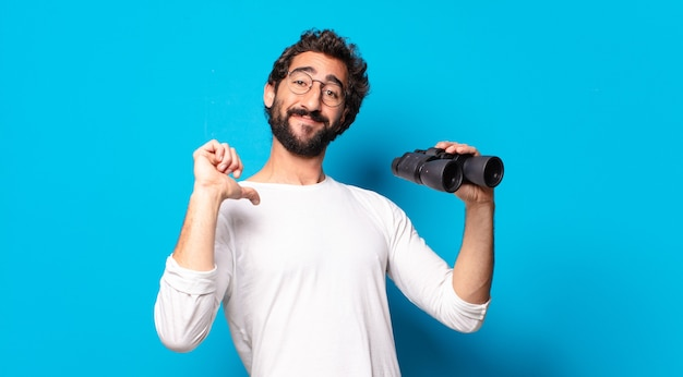 Jeune homme barbu fou avec des jumelles
