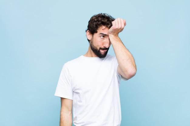 Jeune homme barbu fou levant la paume vers le front pensant oops, après avoir fait une erreur stupide ou se souvenir, se sentir muet contre un mur plat