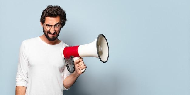 Jeune homme barbu fou avec un mégaphone