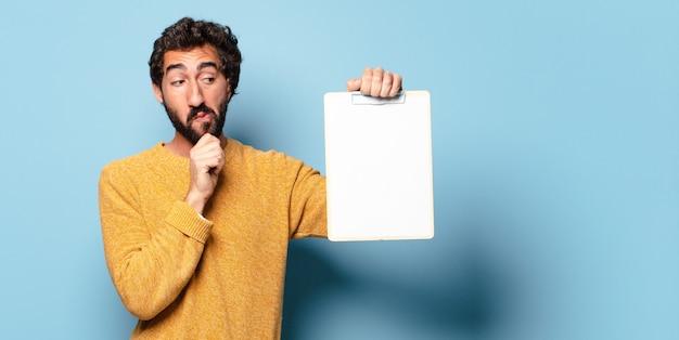 Jeune homme barbu fou montrant une feuille de papier avec un espace de copie