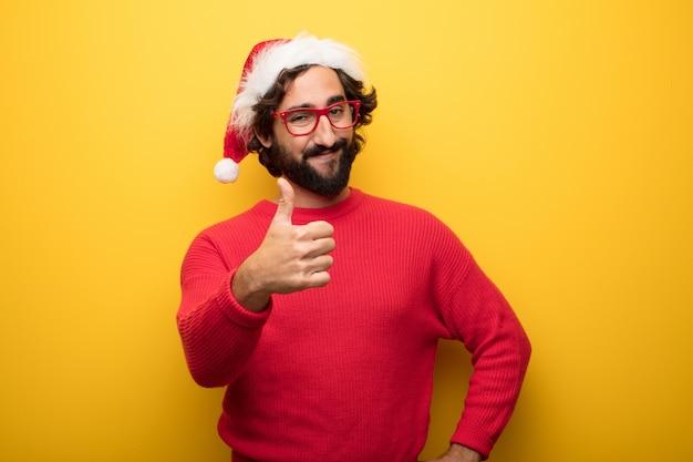 Jeune homme barbu fou portant des lunettes rouges et un chapeau de père noël