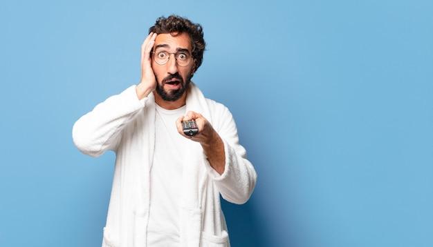 Jeune homme barbu fou portant un peignoir avec une télécommande