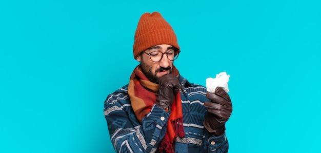 Jeune homme barbu fou et portant des vêtements d'hiver. concept de maladie