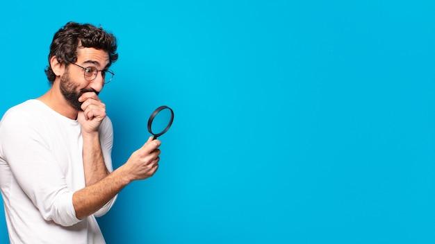 Jeune homme barbu fou regardant et essayant de trouver avec une loupe