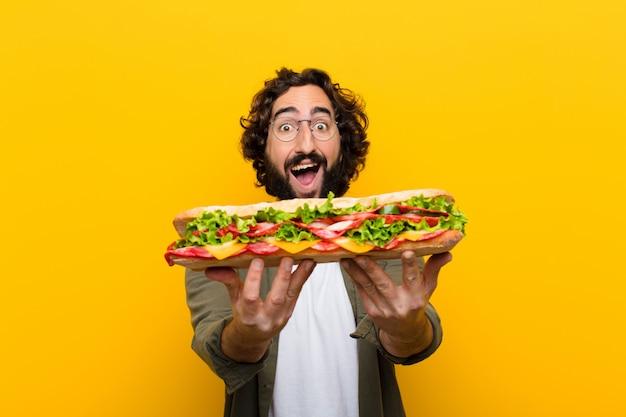 Jeune homme barbu fou avec un sandwich géant.