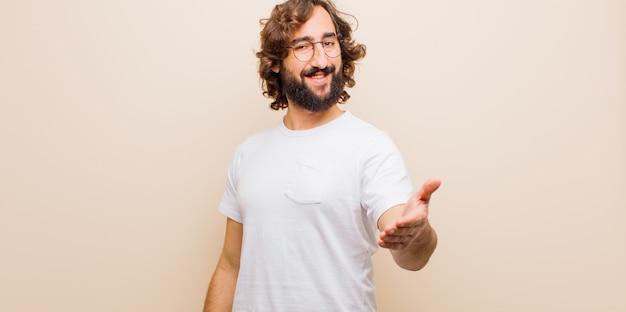 Jeune homme barbu fou souriant, regardant heureux, confiant et amical, offrant une poignée de main pour conclure un accord, coopérant