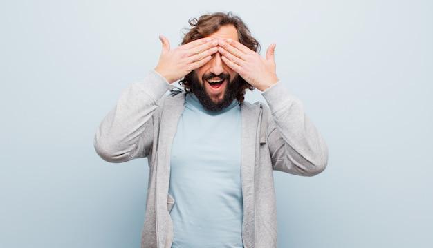 Jeune homme barbu fou souriant et se sentant heureux, couvrant les yeux avec les deux mains et attendant une surprise incroyable contre une couleur unie