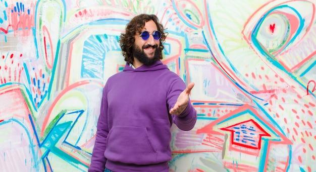 Jeune homme barbu fou souriant, semblant heureux, confiant et amical, offrant une poignée de main pour conclure un accord, coopérant contre le mur de graffitis