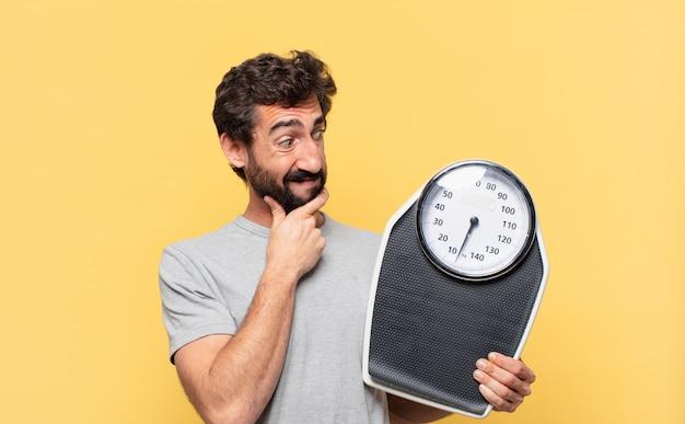 Jeune homme barbu fou suivant un régime doutant ou incertain d'expression et tenant une échelle de poids