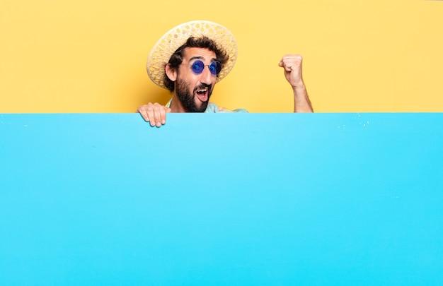 Jeune homme barbu fou avec tableau bleu