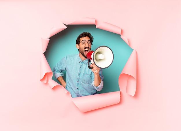 Jeune homme barbu fou tenant un mégaphone dans un trou de papier