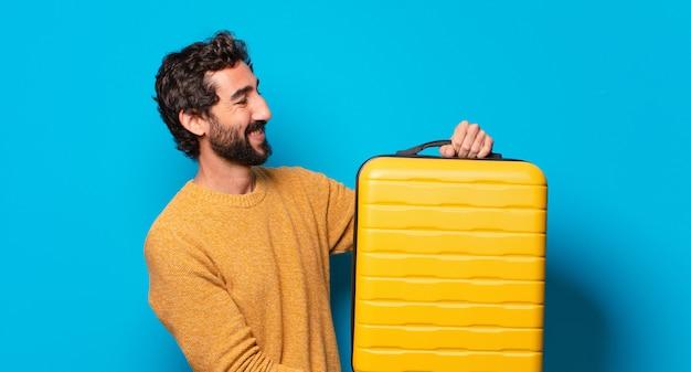 Jeune homme barbu fou avec une valise