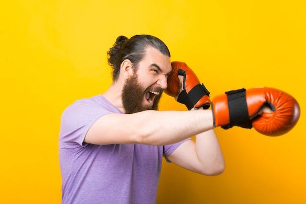 Jeune homme barbu frappant avec des gants de boxe rouges sur fond jaune