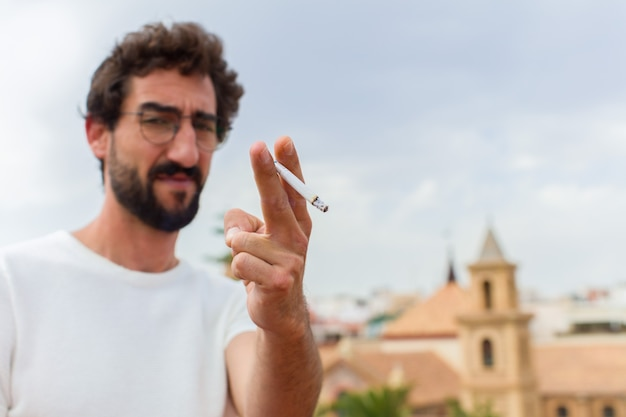 Jeune homme barbu fumant une cigarette