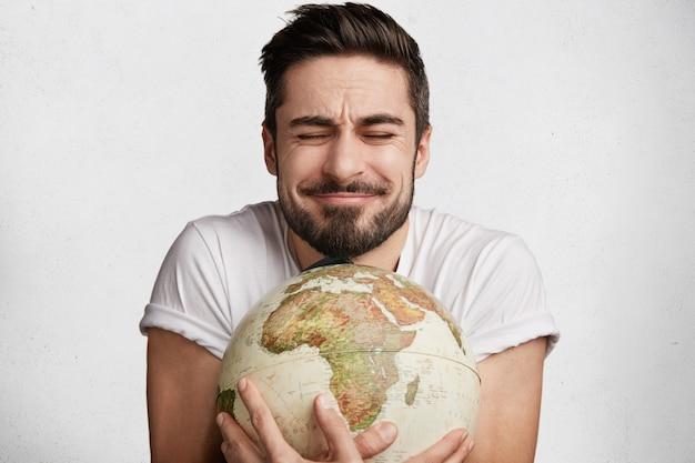 Jeune homme barbu avec globe