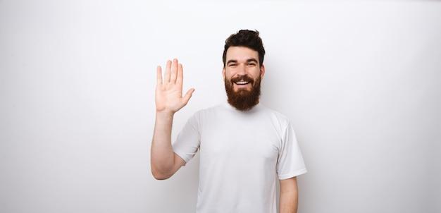 Jeune homme barbu heureux et gai faisant salut, bonjour geste debout sur fond blanc en studio