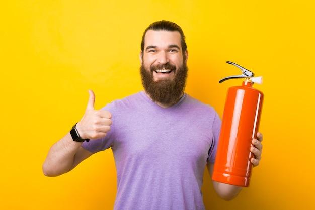 Un jeune homme barbu heureux tient un extincteur et sourit à la caméra tient un pouce vers le haut