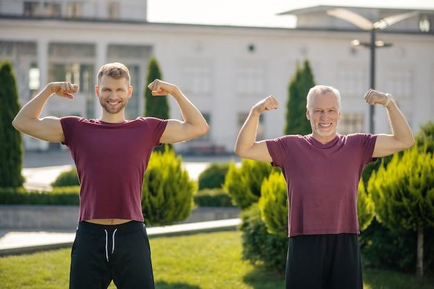 Jeune homme barbu et homme aux cheveux gris mature debout, montrant les biceps
