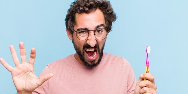 Jeune homme barbu hurlant de panique ou de colère, choqué, terrifié ou furieux, avec les mains à côté de la tête