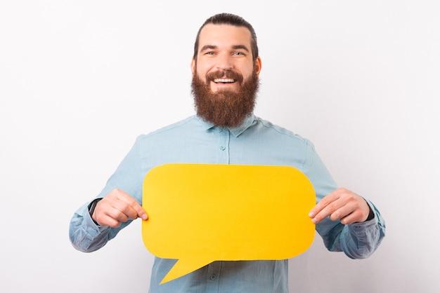 Un jeune homme barbu joyeux tient une bulle de dialogue devant lui.